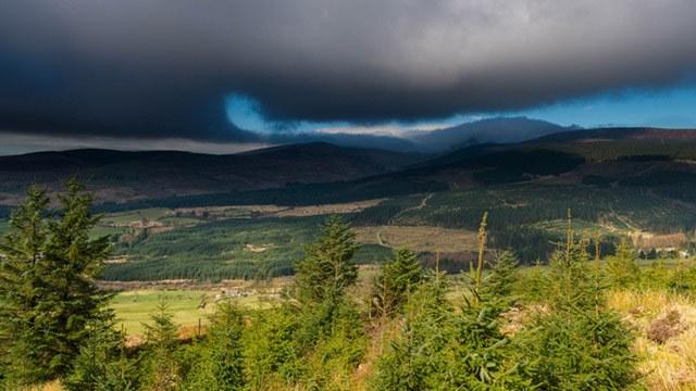 Dark clouds breaking over mountain image